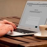 human-using-laptop-beside-teacup-on-the-wooden-table-221043