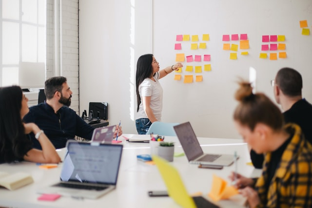 Woman placing sticky notes on wall in business meeting