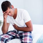 Young,Man,Sitting,With,Stomach,Pain,On,Bed,In,Bedroom